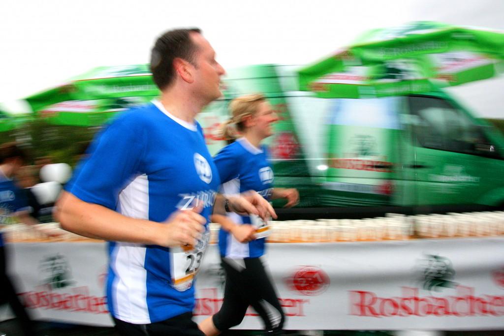 """Zwei Läufer passieren einen Getränkestand beim 5. Firmenlauf Bonn am 08.09.2011 in der Bonner Rheinaue. Der Firmenlauf Bonn ist ein Teamevent und kein Wettkampf. Hier geht es um den Teamgedanken, man lernt die Kollegen und Kolleginnen ganz anders kennen, das fördert das Miteinander und das """"Wir-Gefühl"""" in den Unternehmen. Einen neuen Rekord brachte der 5. Firmenlauf Bonn bei der Teilnehmerzahl mit 6250 Läufer und Walkern und bei der Spendensumme zugunsten der beiden Bonner Hilfsorganisationen CARE und Mukoviszidoese e.V. in Höhe von insgesamt 16.498 €. Weitere Informationen auf www.fila-bonn.de"""
